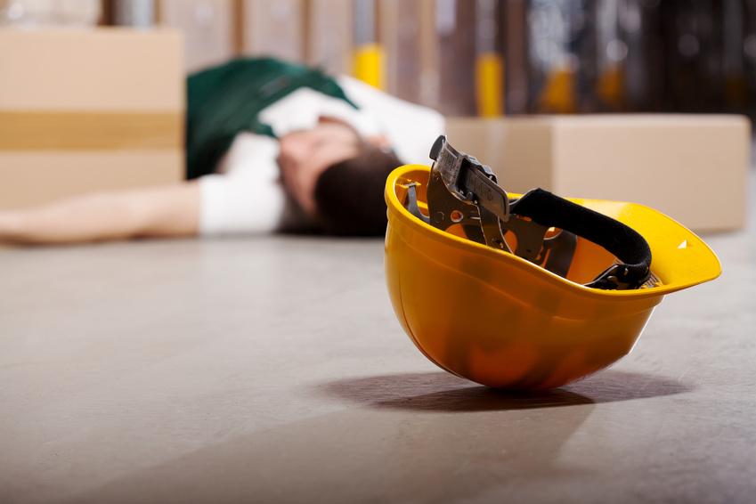 Wypadek przy pracy - omdlały pracownik leżący na ziemi