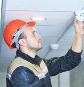 Outsourcing ppoż, pracownik w kasku instaluje detektor dymu