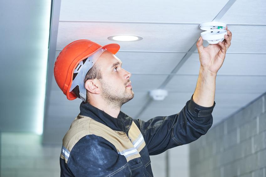 Obsługa ppoż, pracownik w kasku instaluje detektor dymu